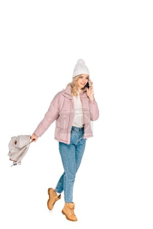 beautiful smiling young woman holding backpack and talking by smartphone isolated on white