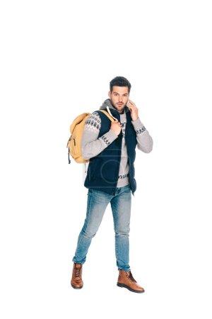 Photo pour Beau jeune homme avec sac à dos parler de smartphone et regardant la caméra isolé sur blanc - image libre de droit