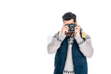 young man with backpack photographing with camera isolated on white