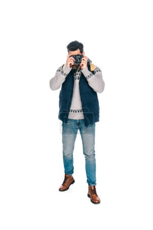 full length view of young man with backpack photographing with camera isolated on white