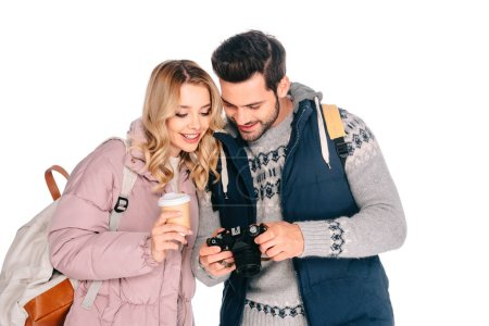 smiling young couple of tourists with backpacks looking at camera isolated on white