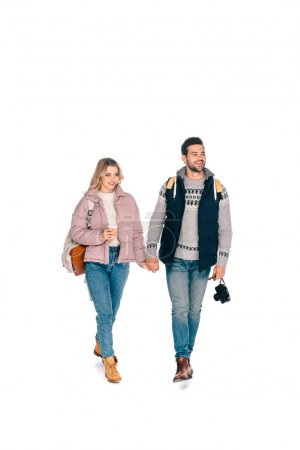 full length view of smiling young couple of tourists with backpacks holding camera and coffee to go isolated on white