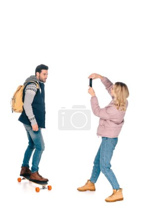young woman with smartphone photographing handsome man with backpack riding longboard