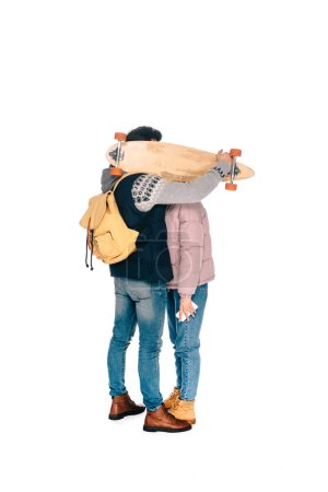 full length view of young couple hiding faces behind longboard isolated on white