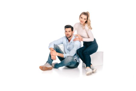 beautiful young couple sitting together and smiling at camera isolated on white
