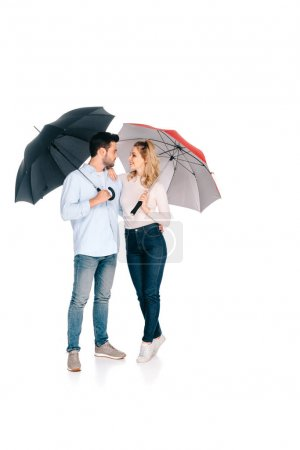 beautiful young couple holding umbrellas and smiling each other isolated on white