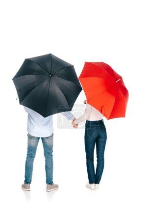 Photo pour Vue arrière du jeune couple avec des parasols noirs et rouges, tenant par la main isolé sur blanc - image libre de droit