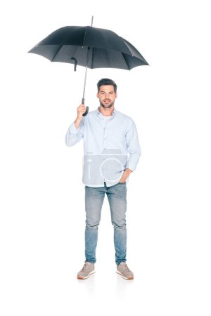 full length view of handsome young man holding black umbrella and looking at camera isolated on white
