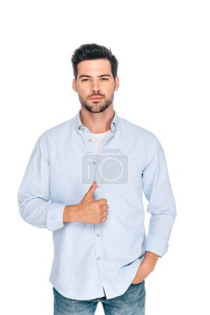 handsome young man showing thumb up and looking at camera isolated on white