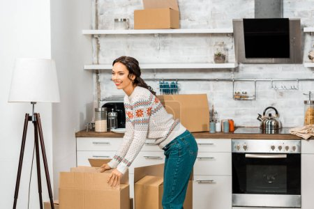 Photo for Attractive young woman standing near cardboard boxes in kitchen at new home - Royalty Free Image
