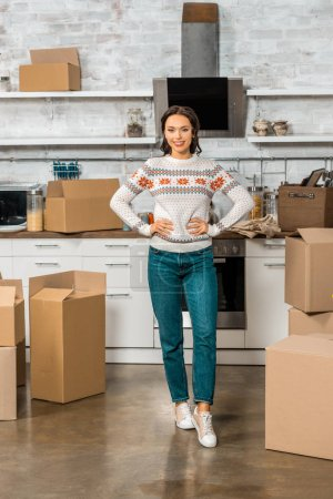 Photo for Young woman standing with hands on waist near cardboard boxes in kitchen at new home - Royalty Free Image