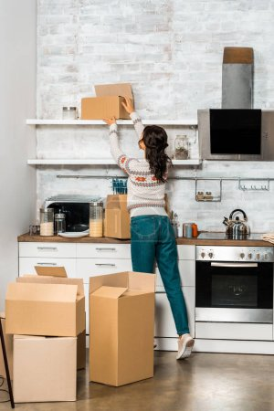 rear view of young woman taking cardboard box from shelf in kitchen at new home