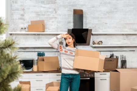 tired pretty woman holding cardboard box and wiping forehead in kitchen at new home