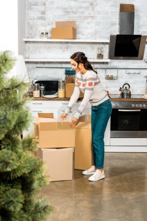 selective focus of woman standing near cardboard boxes in kitchen with christmas tree during relocation at new home
