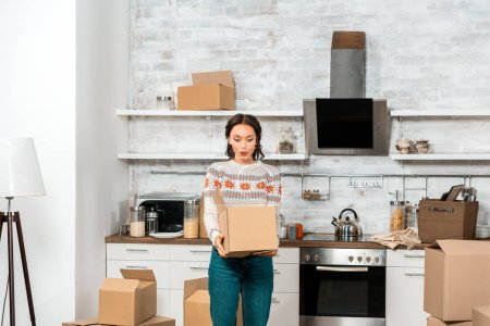 surprised young woman looking into cardboard box in kitchen at new home