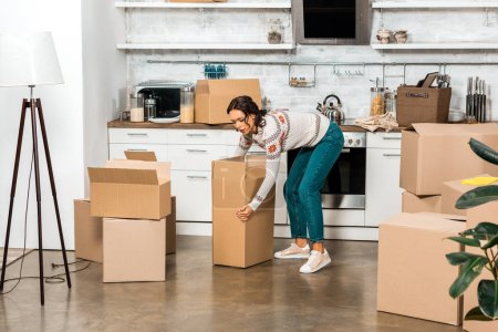 Photo for Young woman taking cardboard box during relocation in new home - Royalty Free Image