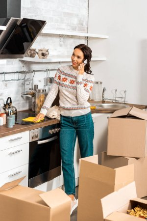 Photo for Young attractive woman talking on smartphone in kitchen with cardboard boxes during relocation in new home - Royalty Free Image