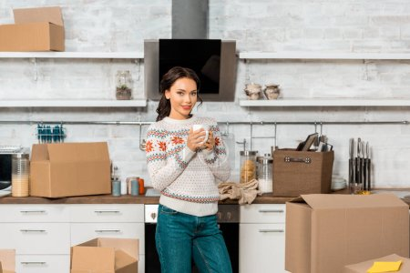 Photo for Selective focus of beautiful woman holding cup of coffee in kitchen with cardboard boxes during relocation in new home - Royalty Free Image