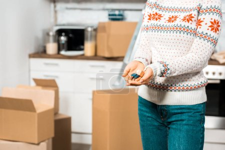 cropped image of woman holding keys in kitchen with cardboard boxes at new home