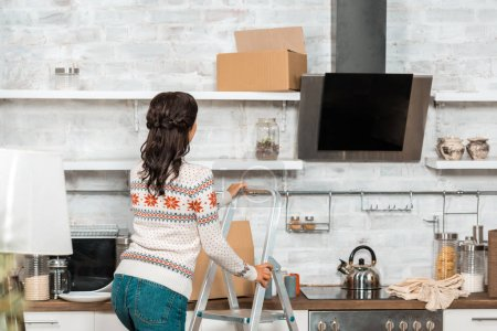 rear view of woman standing on ladder in kitchen during relocation at new home