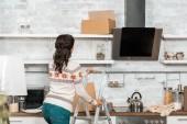 """Постер, картина, фотообои """"вид сзади женщина, стоя на лестнице в кухне во время переезда в новый дом"""""""