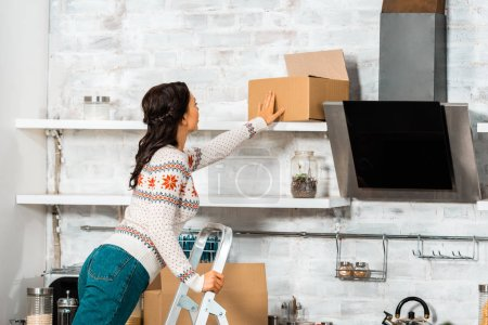 Photo for Rear view of woman putting cardbord box on shelf in kitchen during relocation at new home - Royalty Free Image