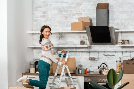 laughing young woman standing on ladder in kitchen with cardboard boxes during relocation at new home