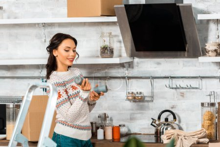 Photo for Attractive smiling woman holding candles in kitchen near ladder during relocation at new home - Royalty Free Image