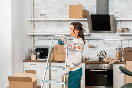 side view of young woman in working gloves carrying ladder in kitchen during relocation at new home