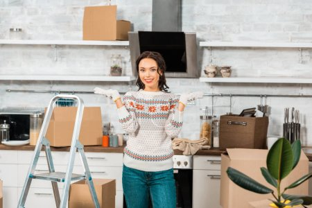 beautiful young woman in working gloves doing shrug gesture near ladder in kitchen during relocation in new home