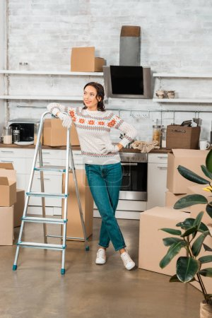 young woman in working gloves standing near ladder in kitchen with cardboard boxes at new home