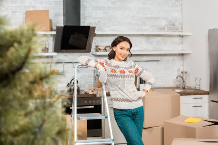 happy young woman in working gloves standing near ladder in kitchen with cardboard boxes at new home