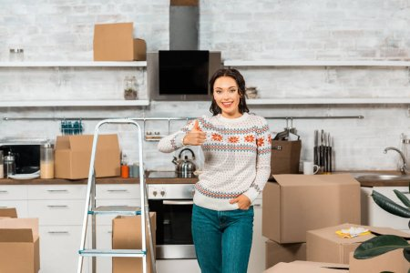 smiling young woman doing thumb up gesture near ladder in kitchen at new home