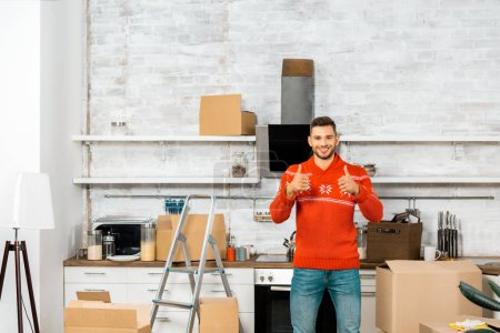 Photo for Happy young man doing thumbs up in kitchen with cardboard boxes during relocation in new home - Royalty Free Image