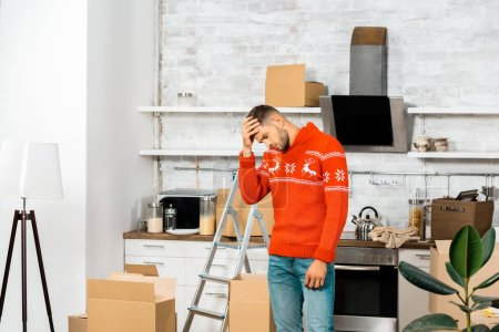 Photo for Upset young man holding forehead in kitchen with cardboard boxes during relocation in new home - Royalty Free Image