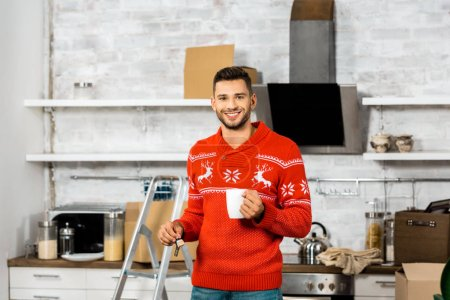 Photo for Cheerful man with coffee cup showing keys in kitchen with cardboard boxes during relocation in new home - Royalty Free Image