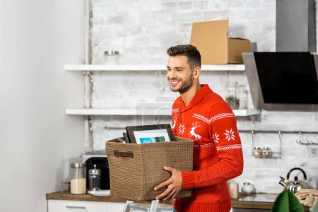 Photo for Happy young man carrying box in kitchen during relocation in new home - Royalty Free Image