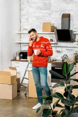smiling man with coffee cup talking on smartphone in kitchen with cardboard boxes during relocation in new home