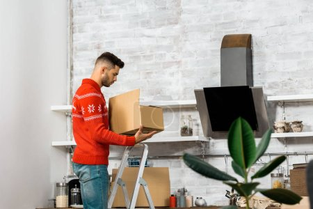 Photo for Side view of man standing on ladder with cardboard box in kitchen during relocation in new home - Royalty Free Image
