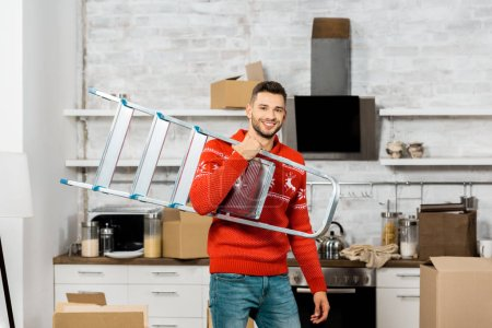 cheerful young man carrying ladder in kitchen with cardboard boxes during relocation in new home