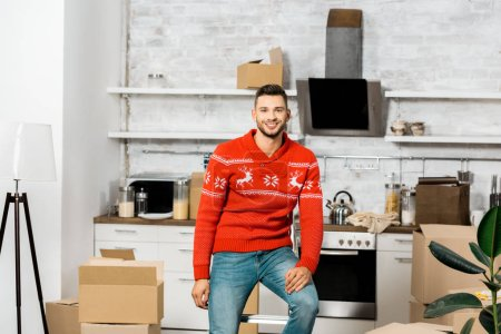 Photo for Happy young man sitting on ladder in kitchen with cardboard boxes during relocation in new home - Royalty Free Image