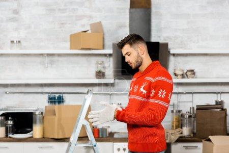 Photo pour Vue latérale du beau jeune homme, mettre des gants de travail en cuisine avec échelle et carton boîtes pendant le déménagement dans la nouvelle maison - image libre de droit