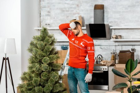 tired man in working gloves wiping forehead near christmas tree in kitchen at home