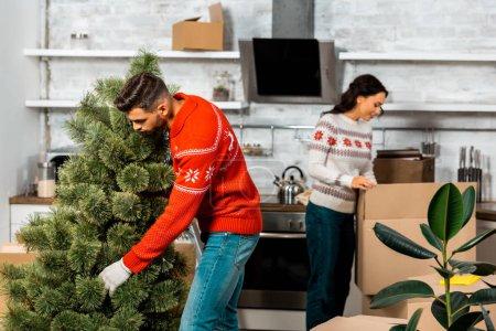 Junger Mann stellt Weihnachtsbaum in Küche, während seine Freundin zu Hause hinter ihm steht