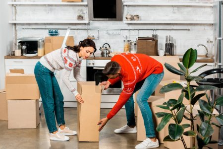 Photo for Serious young couple carrying cardboard boxes for relocation in new home - Royalty Free Image
