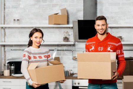 Photo for Smiling young couple carrying cardboard boxes for relocation in new home - Royalty Free Image