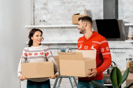 Photo for Happy young couple carrying cardboard boxes for relocation in new home - Royalty Free Image