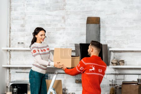 young couple carrying cardboard boxes for relocation in new home