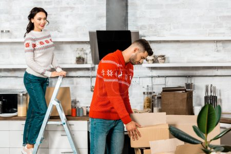 Photo for Handsome young man taking cardboard box while his girlfriend standing on ladder behind in new home - Royalty Free Image