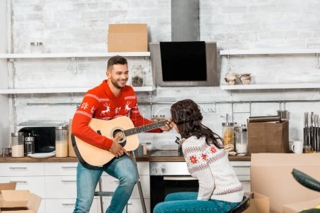 Photo for Laughing young man playing on acoustic guitar to girlfriend sitting in kitchen of new home - Royalty Free Image